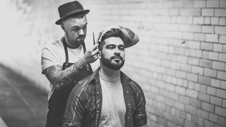 Black and white photo of a man with a beard getting his hair cut by a barber. The barber is holding a comb and a pair of scissors, has tattoos on his arm and is wearing a bowler hat.